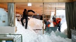 Workers shovel snow out of a restaurant after an avalanche in Switzerland