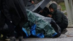 Kurdish migrants from Iran take shelter from the rain, after the dismantling of a camp in Calais