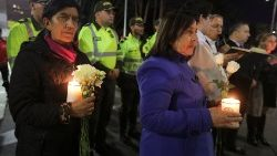 People take part in a candlelight vigil to honor victims, close to the scene of a car bomb explosion, in Bogota