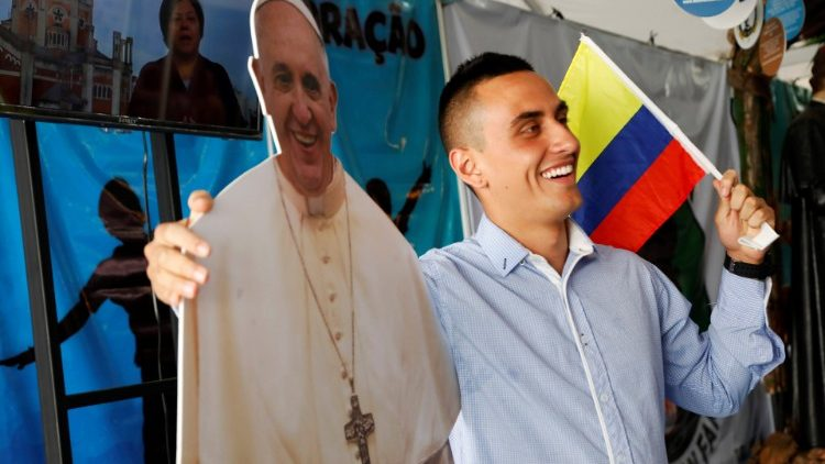 A Catholic pilgrim poses with a cardboard cutout of Pope Francis during an event at a park, ahead of Pope Francis' visit for World Youth Day in Panama City