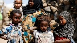 Children stand at a makeshift camp for internally displaced people near Sanaa, Yemen