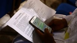 A person studying the Bible on their mobile phone