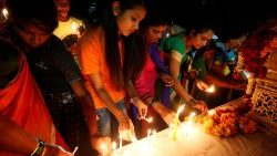 People light candles at a memorial during a vigil after a suicide bomber rammed a car into a bus in south Kashmir last week, in Ahmedabad