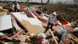 People look through the wreckage of their friend's home after two back-to-back tornadoes touched down, in Beauregard