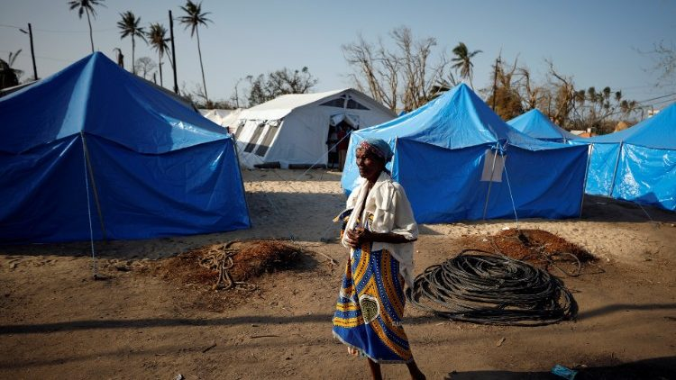a-woman-walks-past-tents-in-a-camp-for-people-1553796548601.JPG
