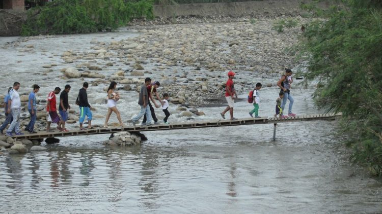 People walk on a makeshift bridge to cross the Tachira River on the Colombian-Venezuelan border, as seen from the outskirts of Cucuta