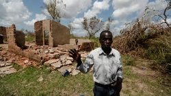 A Mozambican man in front of his damaged house in the village of Cheia, near Beira
