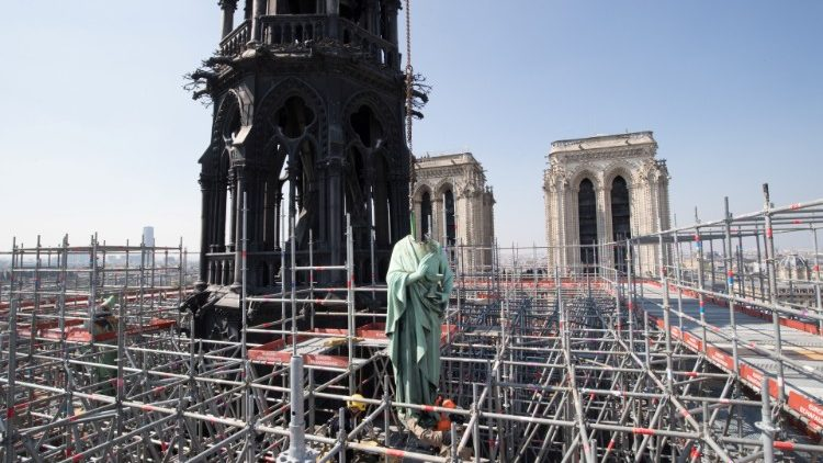 A statue of Saint John is removed from the spire of Notre Dame cathedral by a crane before restoration work, in Paris