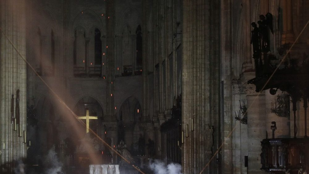 Smoke rises around the alter in front of the cross inside the Notre Dame Cathedral as a fire continues to burn in Paris
