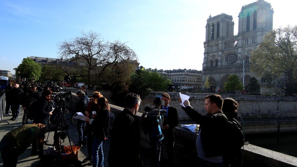 journalists-work-on-a-bridge-near-notre-dame--1555487359758.JPG