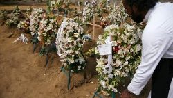 A priest arranges flowers at the site of a mass burial in Negombo, Sri Lanka