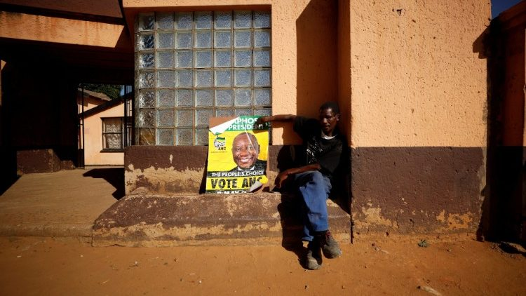 A supporter of President Cyril Ramaphosa's ruling African National Congress (ANC) sits beside a party poster as he awaits election results in Diepkloof township in Johannesburg