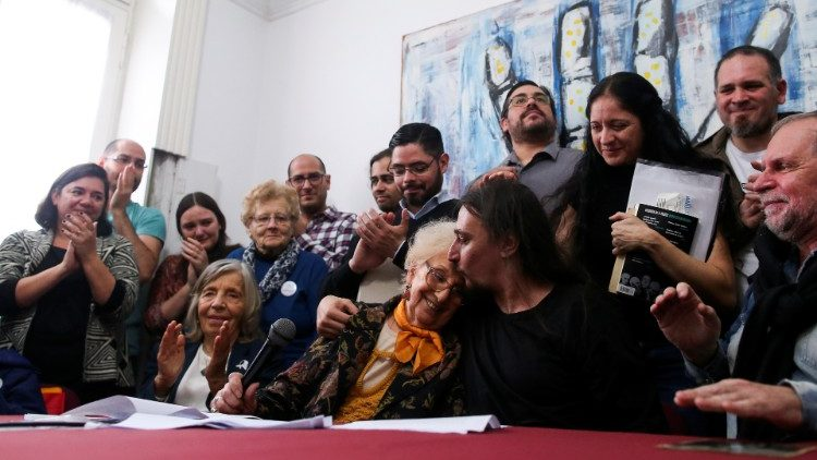 Javier Matias Darroux Mijalchuk, son of Elena Mijalchuk and Juan Manuel Darroux, who disappeared during Argentina's former 1976-1983 dictatorship, comforts the president of human rights organisation de Carlotto, during a news conference in Buenos Aires