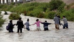 Migrants form a human chain to cross the Rio Bravo to enter into the United States