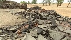 Video grab of a soldier standing near debris from destroyed homes at the site of an ethnic massacre in which gunmen killed dozens of people, in the Dogon village of Sobane Da
