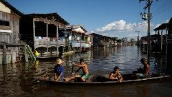 Children paddle their canoe through a street flooded by the rising Rio Solimoes, one of the two main branches of the Amazon River, in Anama