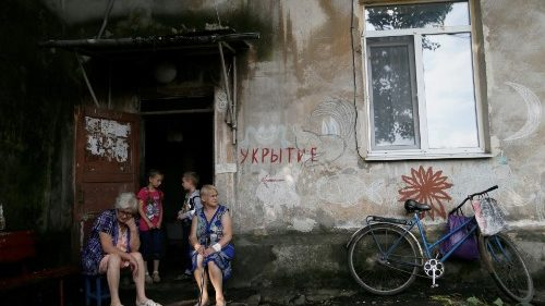 "Local residents outside a bloc of flats in a Donetsk suburg in easter Ukraine. The sign reads ""Shelter""."