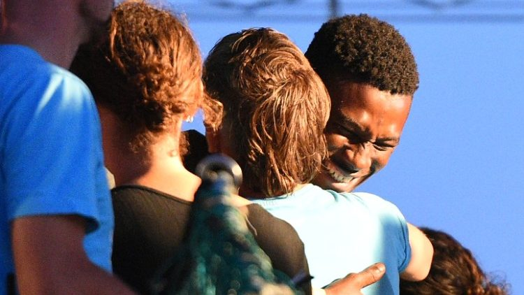 A migrant plucked from the Mediterranean embraces a crew member of a rescue ship