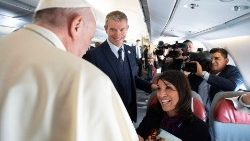 Pope Francis accompanied by a member of the Holy See Press Office Matteo Bruni talks with people on board of a plane to Panama City