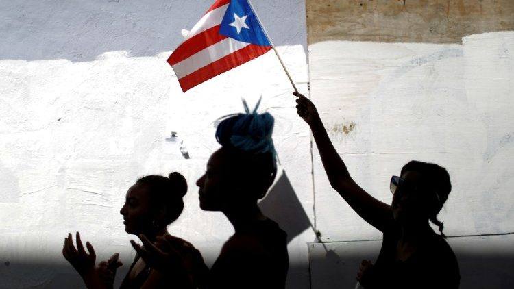 A woman waves a Puerto Rican flag in San Juan, Puerto Rico