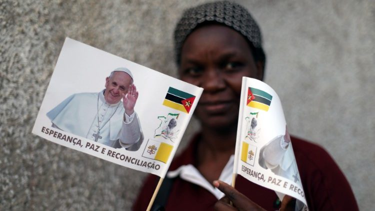 A woman in Maputo poses with flags heralding Pope Francis' visit to Mozambique