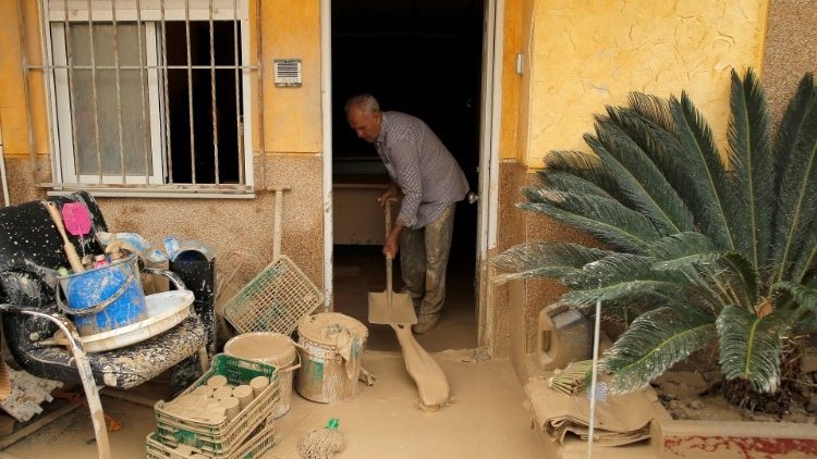 A man removes mud from his house after a flood caused by torrential rains in Orihuela