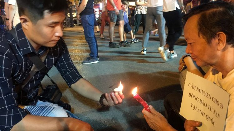Vietnamese residents light candles during a prayer for 39 people found dead in the back of a truck near London, in front of Hanoi Cathedral in Hanoi