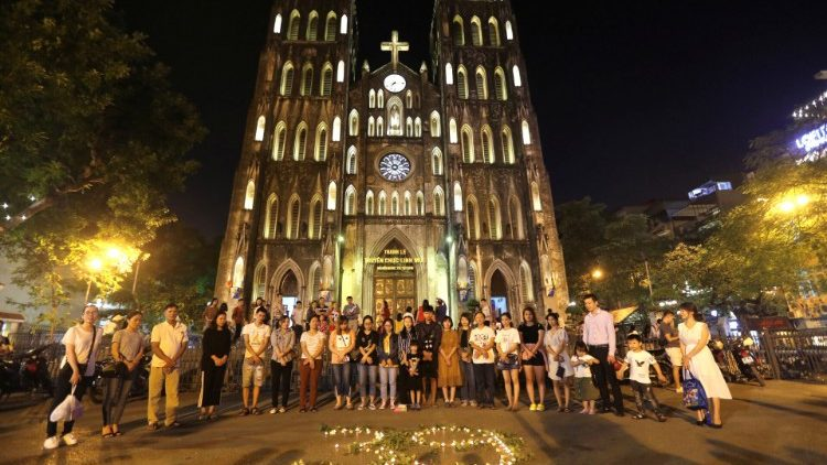 Residents light candles to pray for 39 people found dead in the back of a truck near London, in front of Hanoi Cathedral in Hanoi