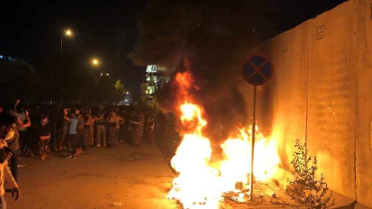 Demonstrators light fires in front of the Iranian consulate in Kerbala
