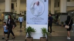 People walk pass a poster of Pope Francis in the Holy Redeemer Church in Bangkok,