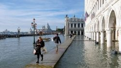 People walk in the flooded St. Mark's Square during high tide in Venice