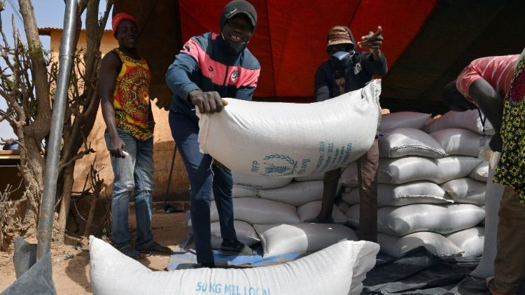 Workers carry the aid provided by the World Food Programme (WFP) for distribution in Pissila,  Burkina Faso