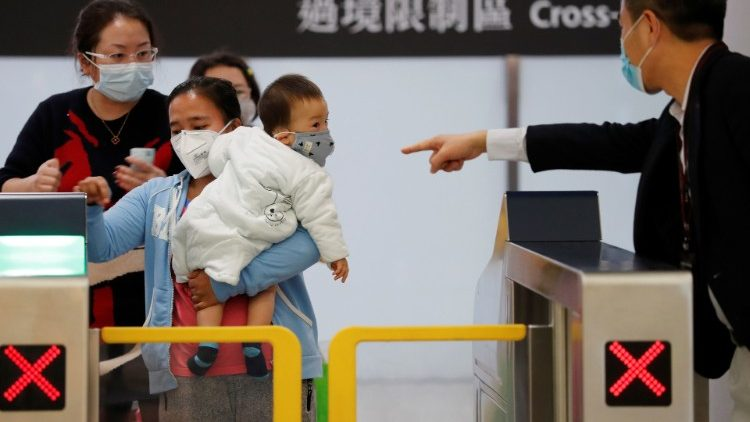 Passengers wear masks to prevent an outbreak of a new coronavirus, as they arrive at Hong Kong West Kowloon High Speed Train Station Terminus, before temporary closing, following the coronavirus outbreak in Hong Kong