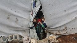 Internally displaced children look out from a tent in Azaz