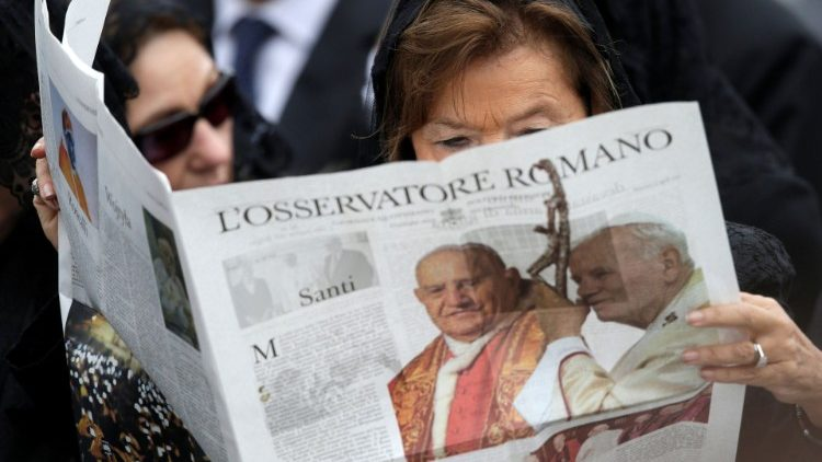 FILE PHOTO: A woman reads a copy of the Vatican newspaper L'Osservatore Romano as she waits for the canonisation ceremony in St Peter's Square at the Vatican