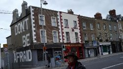 "Passer by walks by building which reads ""Don't be afraid"" amid coronavirus disease (COVID-19) in Dublin"