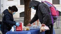 A volunteer hands out breakfast to a man in Rome