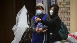 A woman and her child wearing masks to avoid the spread of the coronavirus disease (COVID-19), struggle against strong wind and rain in central Seoul