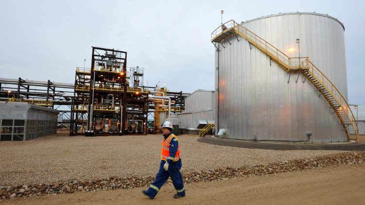 FILE PHOTO: An oilfield worker walks past an oil sands facility