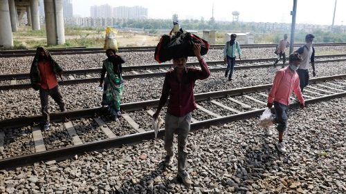 Indian migrant workers carrying their belongings on their way home