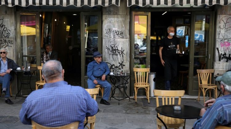 A waiter wearing a masks serves customers in a coffee shop as restaurants reopen, Greece