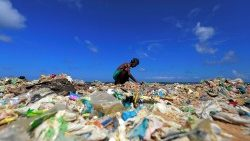A volunteer collects rubbish on the beach on World Environment Day, Sri Lanka