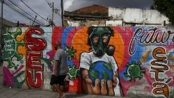 A man walks in front of a graffiti of a boy wearing a face mask in Rio de Janeiro, Brazil