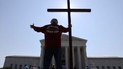 A man holds a cross outside the US Supreme Court