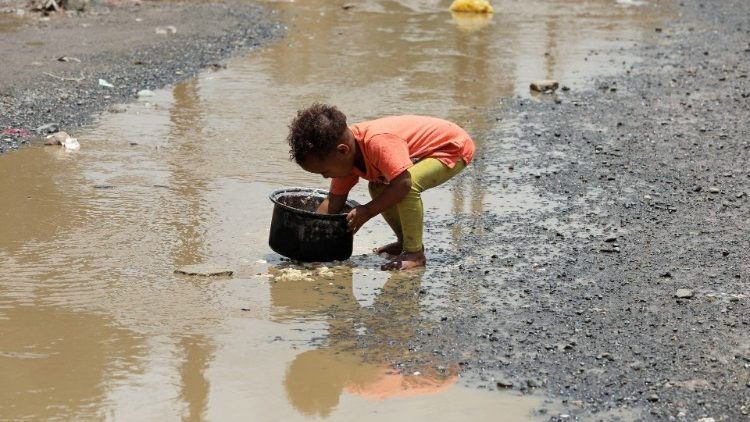 Boy washes a cooking pot in a rain water pool outside a slum area for the Muhamasheen (marginalized) community in Sanaa
