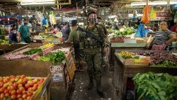 A police officer ensuring Covid-19 health protocols are being observed in a public market in the Philippines.