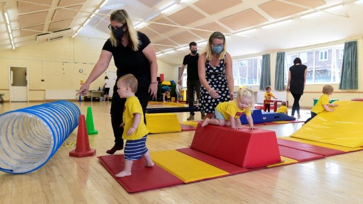 "Children accompanied by adults participate in ""Tumble Tots"" play activity in Gloucester"
