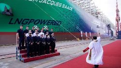 A priest blesses a new French ship built in China ahead of its maiden voyage, at the port of Shanghai.