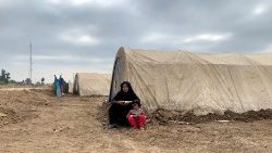 A displaced Iraqi woman and her child sit in front of their tent in an informal camp in the town of Balad