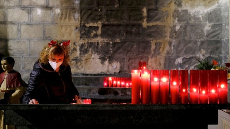 A woman wearing a facemask lights a candle inside a church in Barcelona, Spain